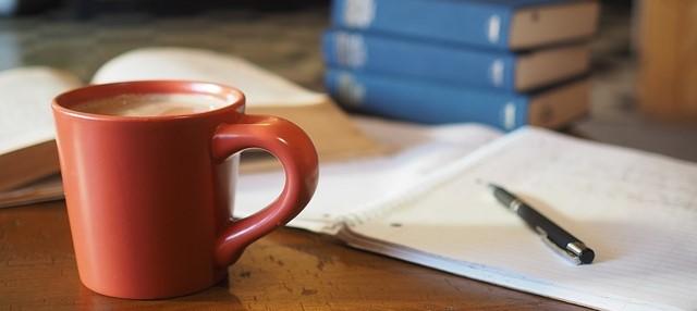 机の上の勉強用具とコーヒー